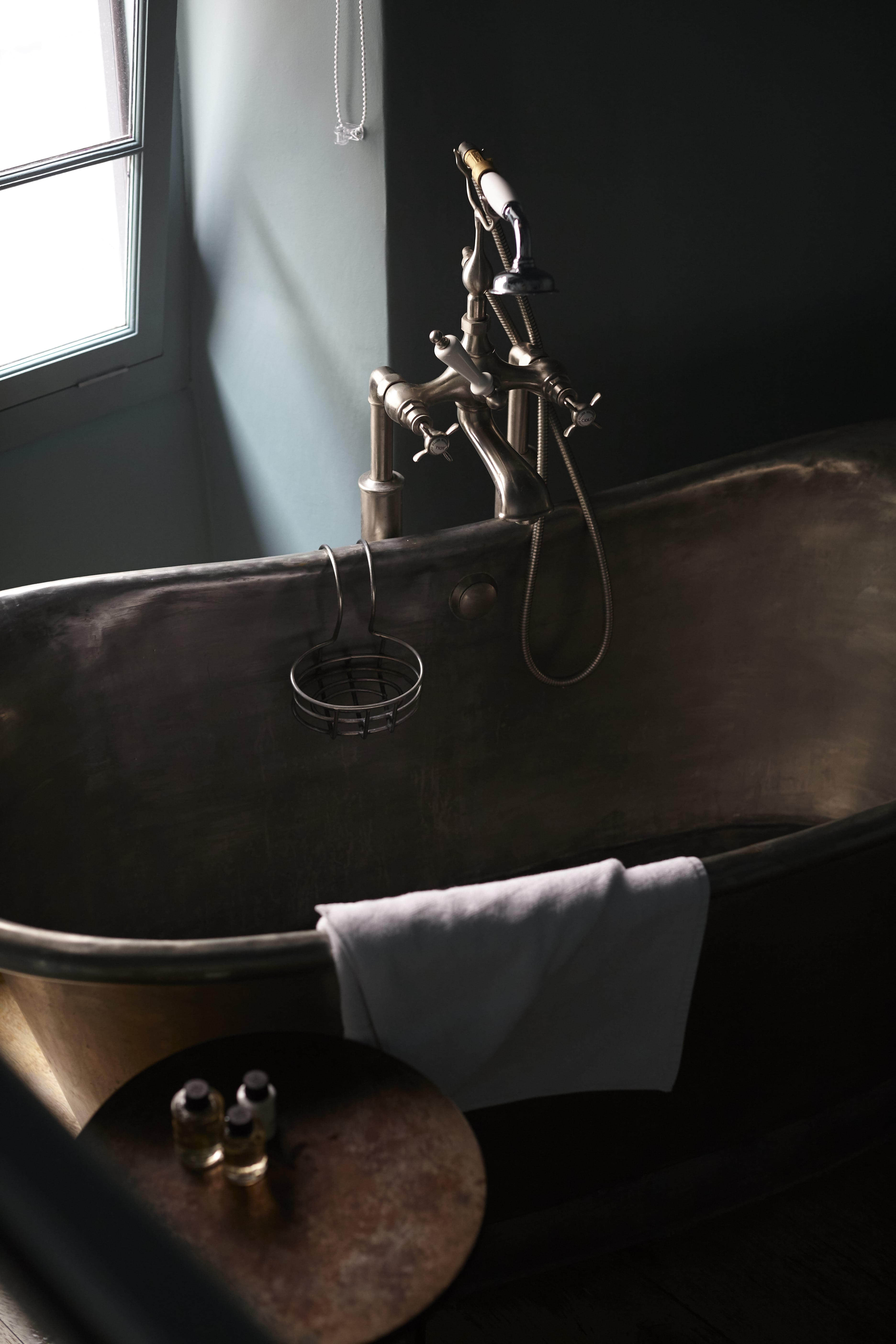 stainless steel bath tub with noble isle bath products and a fresh towel at The Archangel, pub and cocktail bar with bedrooms in Frome, Somerset