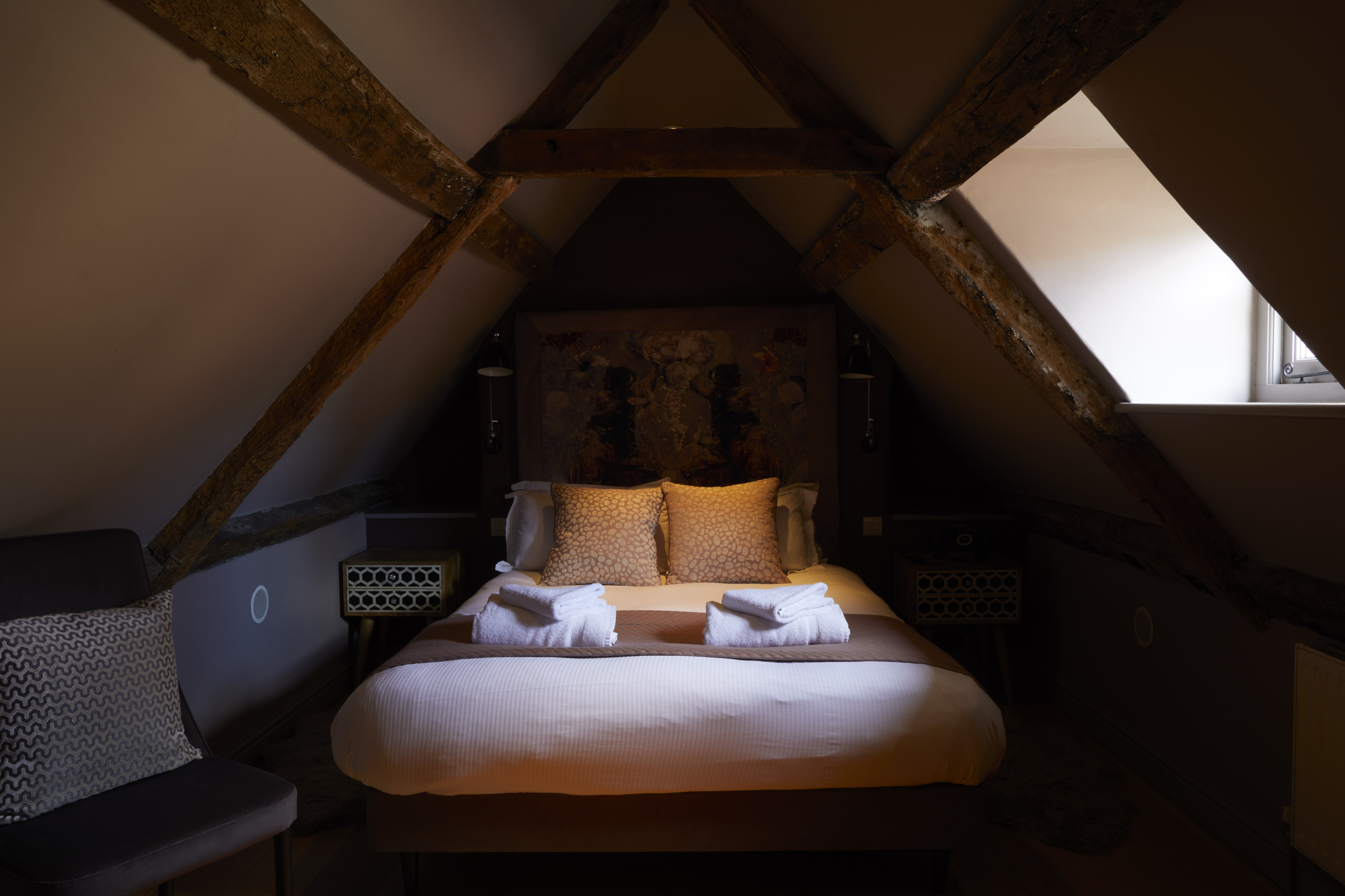 double bed in the eaves with fresh towels at The Archangel, pub and cocktail bar with bedrooms in Frome, Somerset