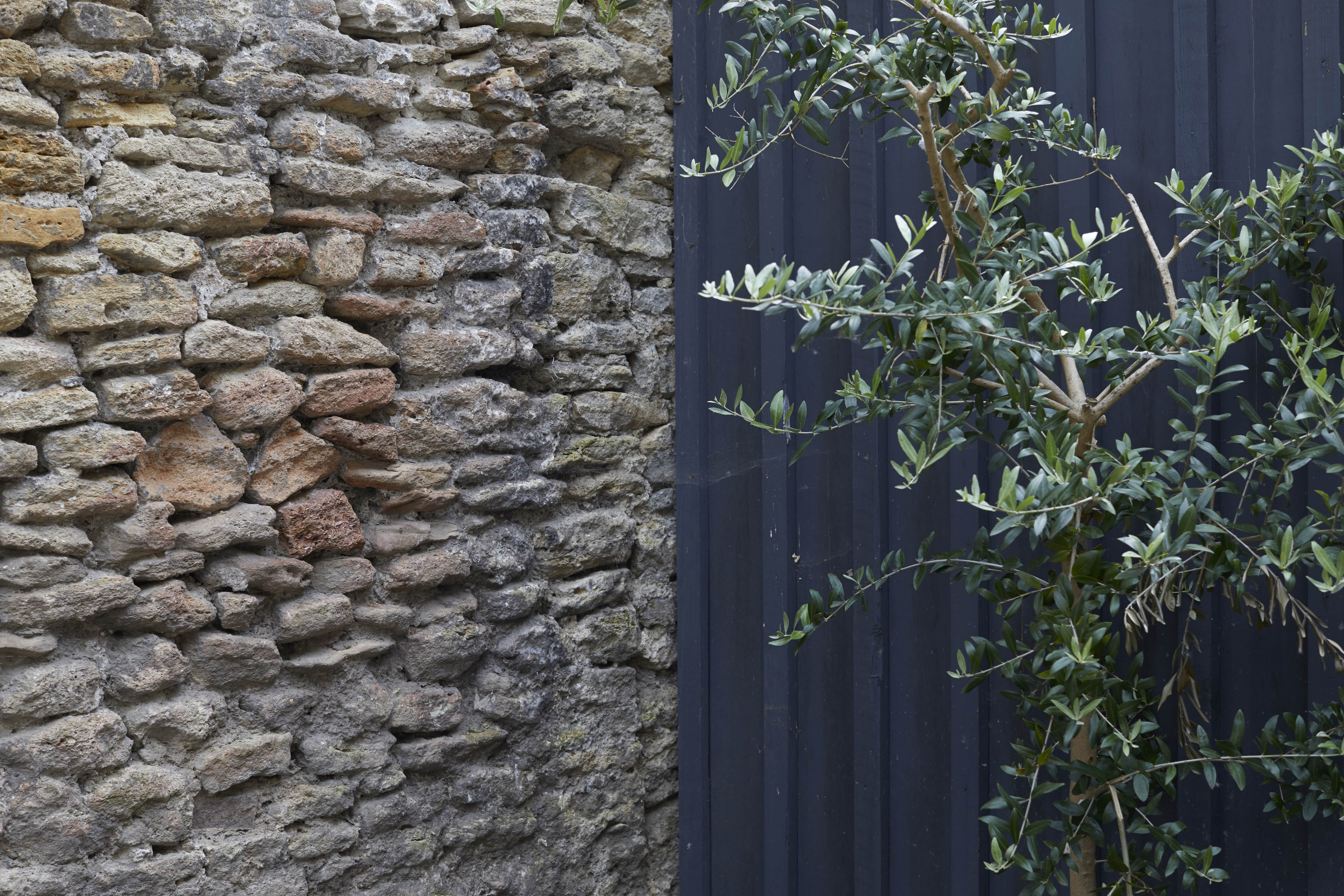 bare brick and steel walls outdoor in the courtyard terrace garden at The Archangel, pub and cocktail bar with bedrooms in Frome, Somerset