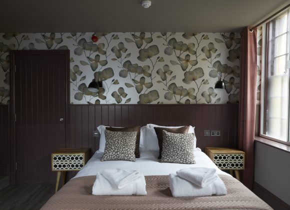 double bedroom with floral wallpaper and fresh towels at The Archangel, pub and cocktail bar with bedrooms in Frome, Somerset