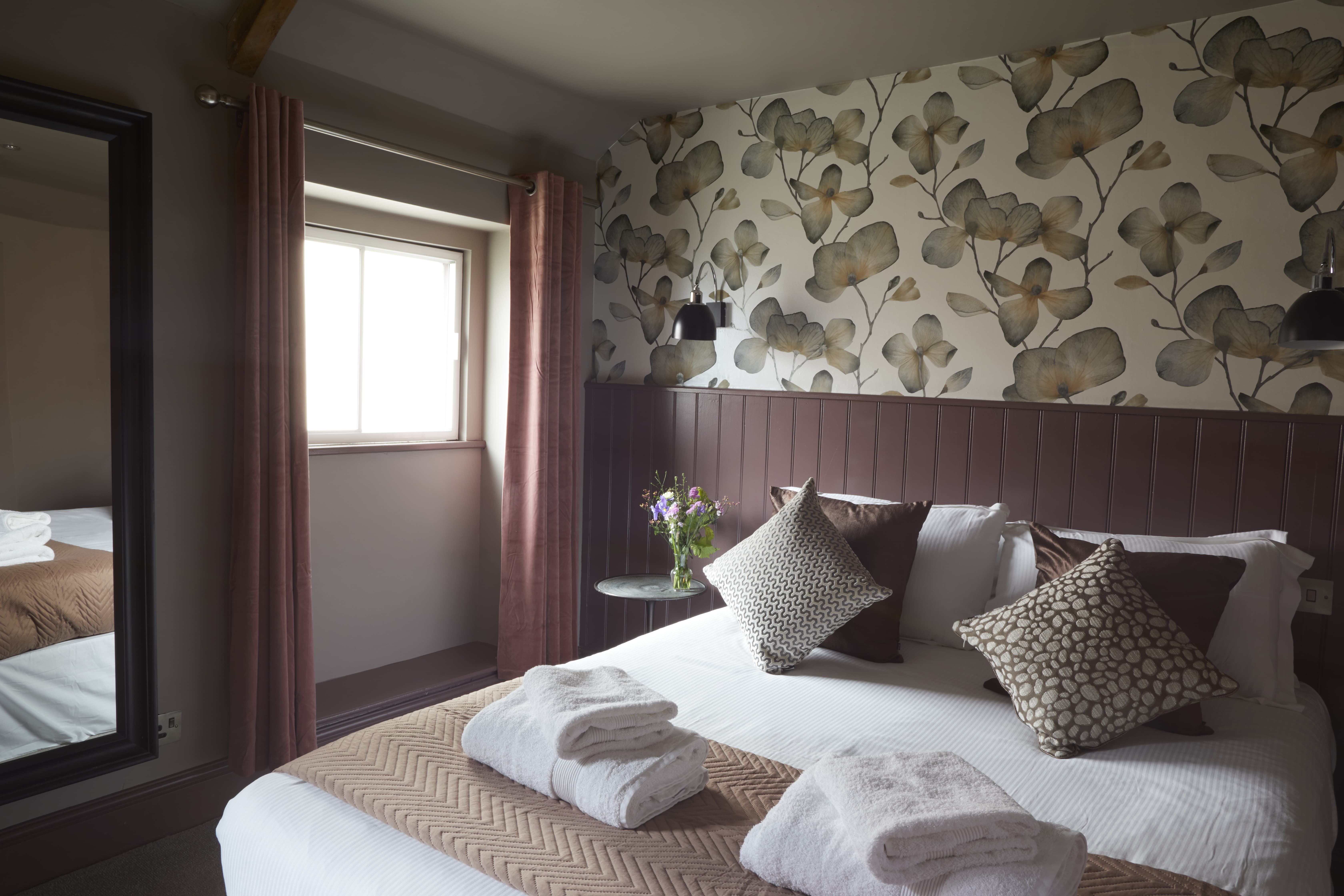 double bedroom with decorative cushions, fresh flowers, fresh towels and floral wallpaper at The Archangel, pub and cocktail bar with bedrooms in Frome, Somerset